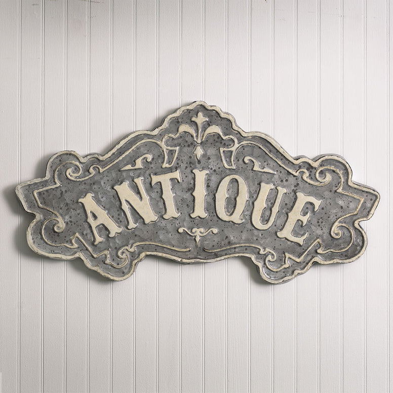 Metal wall sign features a detailed design and the word 'Antique'. Sign has a distressed gray finish.