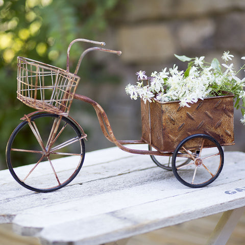 Perfect for adding a small planter into the back, the planter is made of metal and features a rusted finish and black spoked wheels.