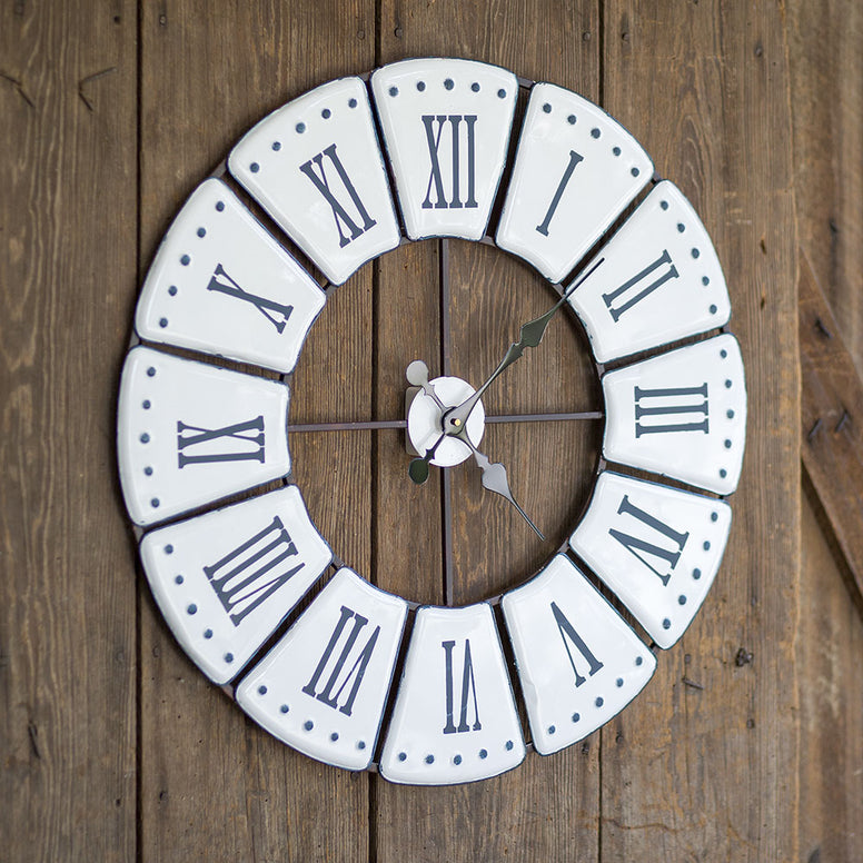 Metal wall clock featuring a distressed black and white finish. Clock design also comes with an open face and Roman numerals.