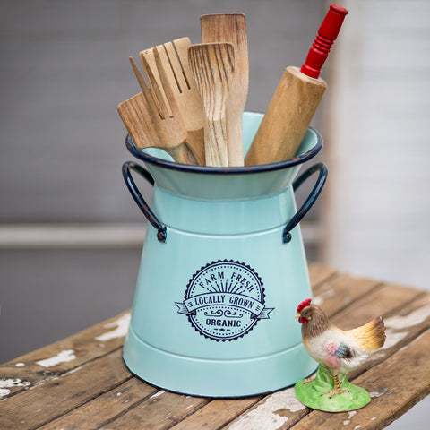 This metal canister has a milk can shape, light and dark blue distressed finish and includes two side handles. Features a vintage scroll design and the messages 'Farm Fresh', 'Locally Grown', and 'Organic""
