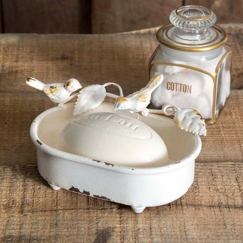 Made of metal, this soap dish has a distressed finish and features a bird and vine design.