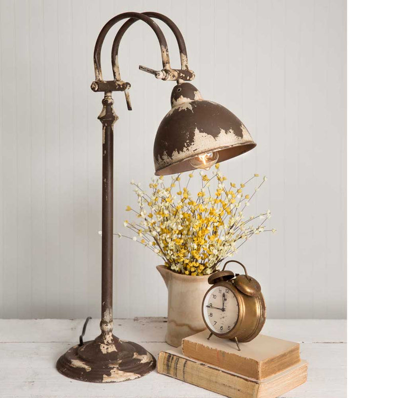 This vintage industrial styled adjustible lamp is made of metal and features a distressed finish.