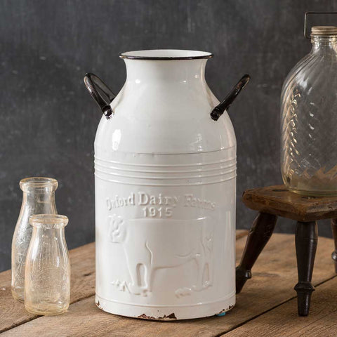 "Perfect for your unique décor, this milk can is made of metal with a distressed white and black finish. Features an ""Oxford Dairy Farms"" design"