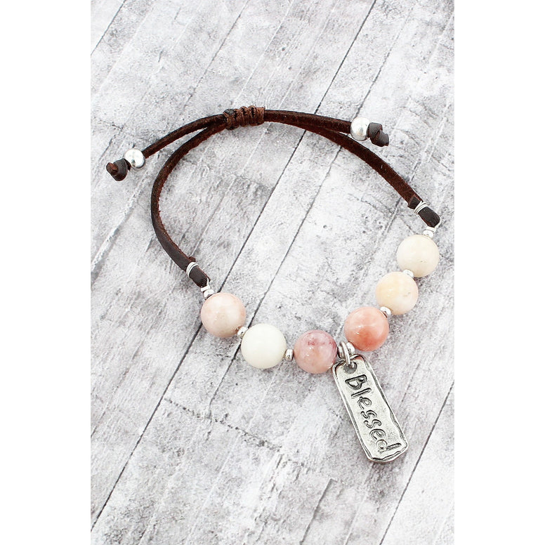 "Light Peach And Cream Natural Bead And Brown Faux Leather Cord Bracelet. 1"" Rectangular Burnished Silver Charm with ""Blessed"" Message."