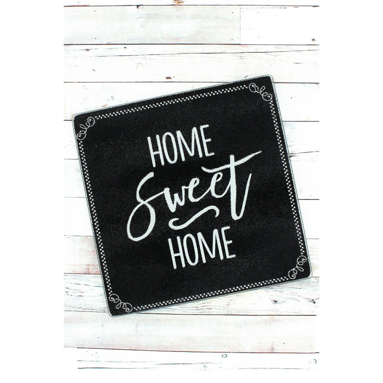 "Black tempered glass cutting board has a white stylized design around the edges and the message ""Home Sweet Home' in white."