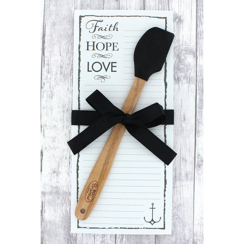 Black and white shopping list magnetic rectangular note pad Has 'Faith, Hope, Love' In Upper Left Corner. Matching black spatula Is attached with a black tied ribbon.