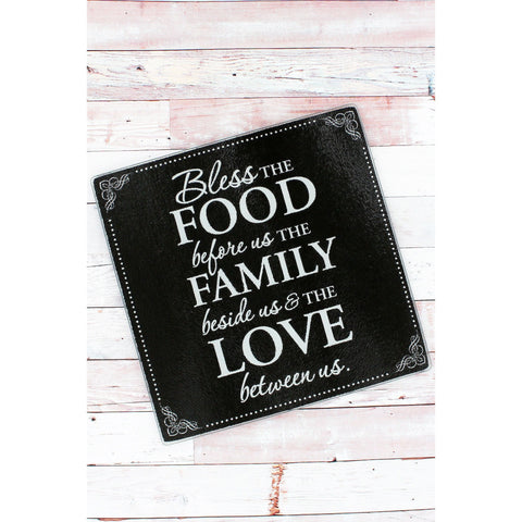 "Black tempered glass cutting board has white stylized design and scripted message ""Bless The Food Before Us The Family Beside Us & The Love Between Us'."