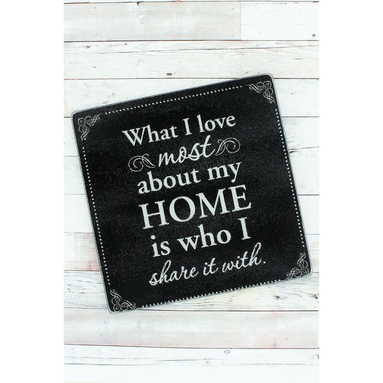 Glass trivet features a black background and stylish border. Message of 'What I Love Most About My Home Is Who I Share It With' is written is various white fonts.