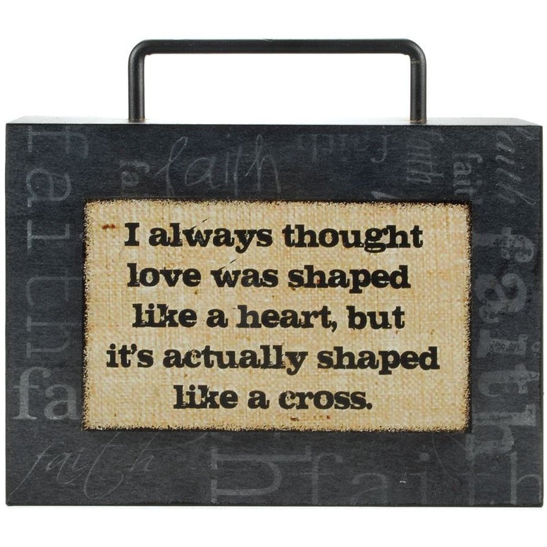 "Box sign bears the message ""I Always Thought Love Was Shaped Like A Heart, But It's Actually Shaped Like A Cross"". The word ""Faith"" is lightly etched on a dark gray background and a handle at the top."