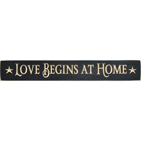 Country primitive style engraved plaque has black distressed finish and message 'Love Begins At Home'. Accented with stars.