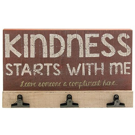 Rustic style clipboard features the message 'Kindness Starts With Me - Leave Someone A Compliment Here'.  Made of distressed wood, this board has three black metal clips to hold the compliments.