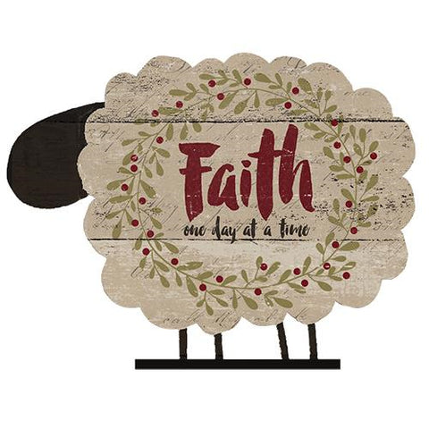 "Made of wood, this fun cut out sheep features a distressed white background and the phrase ""Faith one day at a time"" in red and black script."