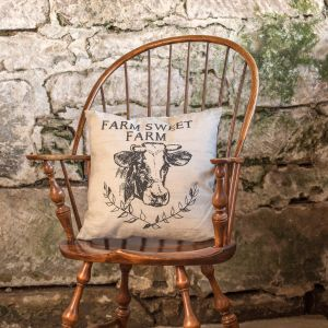 Pillow has an overall distressed finish with a white background and black vine and cow design. the pillow also features the message 'Farm Sweet Farm' in block letters across the top.