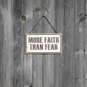 Made of metal, this sign features a distressed finish with a white background and black design with the message 'More Faith Than Fear'. Sign hangs from a metal chain that adds a vintage industrial touch.