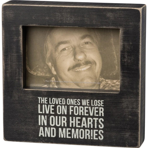 "This photo frame features a distressed black background and white lettering that bears the message ""The Loved Ones We Lose Live On Forever In Our Hearts And Memories""."