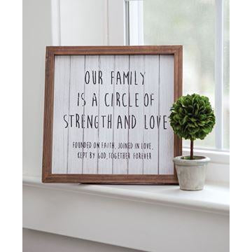 This framed sign features vertical wood slats that are painted white and slightly distressed. Natural-looking large black text spells out the message 'Our family is a circle of strength and love'. The sign then includes in small text the phrase 'Founded on faith, joined in love, kept by God, together forever'.