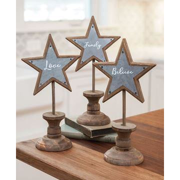 These trendy farmhouse industrial star spindles are made of natural wood, with galvanized metal accents. Each star features a phrase in whimsical white lettering that says either 'Family', 'Love', or 'Believe'.