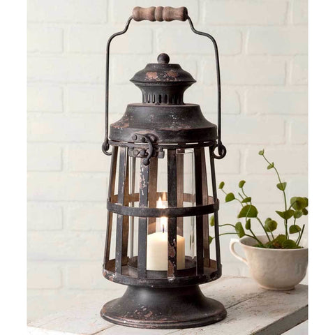 This candle lantern is made from metal and features a wooden handle and distressed black finish