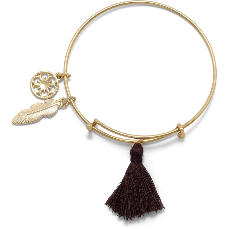 Gold tone bangle expandable style bracelet has a 12.4 mm round flower charm, a feather charm and a chocolate brown tassle.