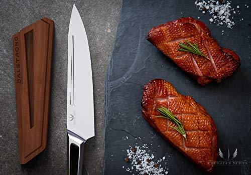 Chef knife with stainless stell handle next to some uncooked meat