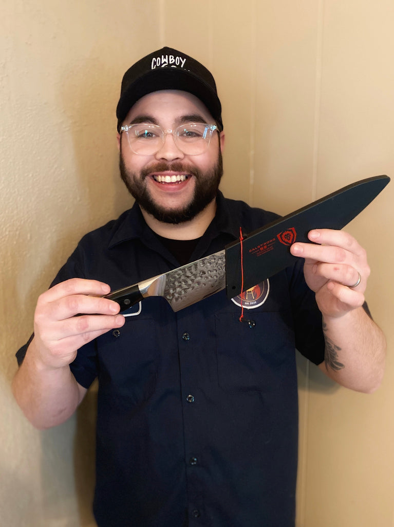 Jesse Stanley (@pitmasterpastor) holding a Dalstrong shogun chef knife