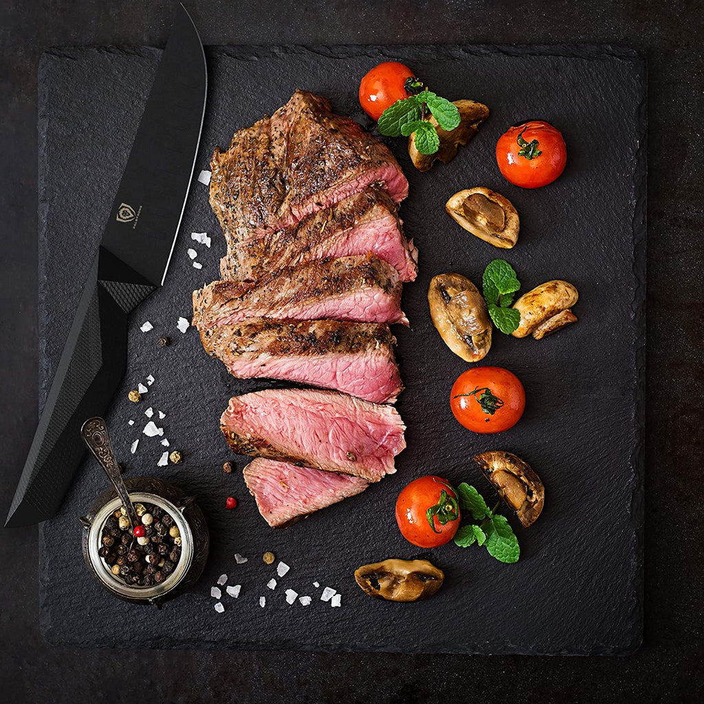 A black cutting board of pink cooked steak next to a black steak knife surrounded by garnish