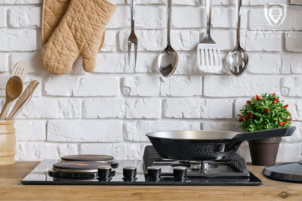 Black skillet it on a kitchen stove with kitchen utensils a oven gloves in the background