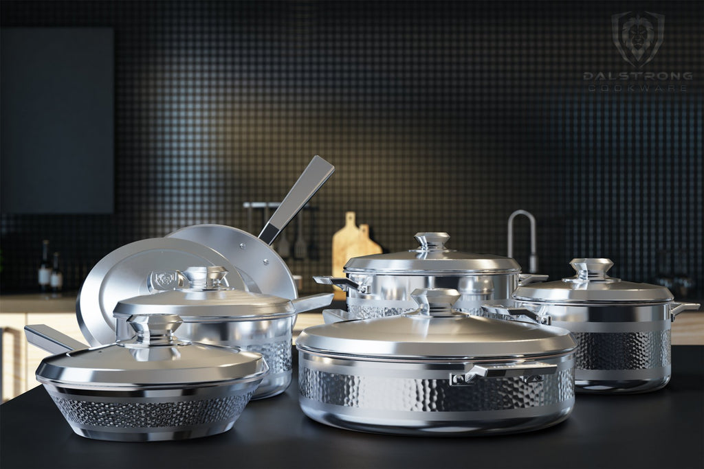 12 piece of silver cookware on a kitchen countertop with black tiled walls in the background