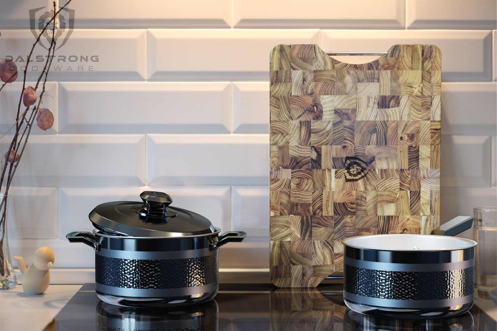 Two black pots on an induction stove top with a wooden cutting board leaning against the background wall