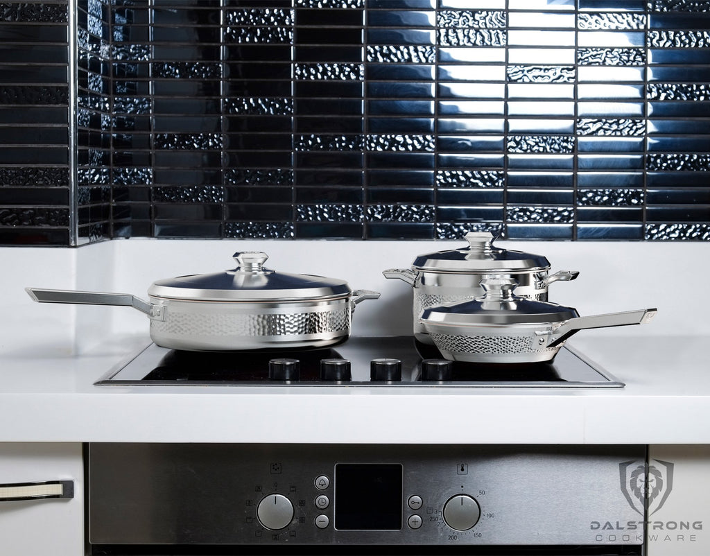 Three silver pieces of cookware on a stove induction top in a white and black kitchen