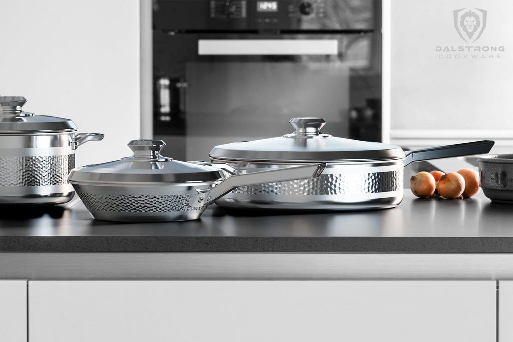 Stainless steel cookware on a dark kitchen counter with an oven in the background