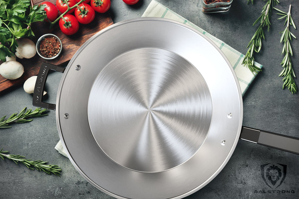 Stainless Steel frying pan skillet covering most of a tea towel on a dark granite counter that is littered with tomatoes, garlic and other garnish