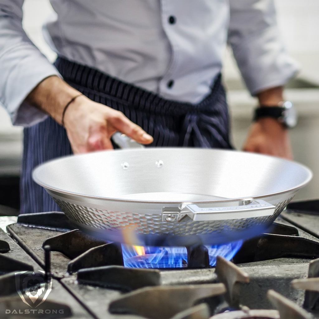 A chef in a navy blue apron holds a stainless steel frying pan skillet over a naked flame in a kitchen