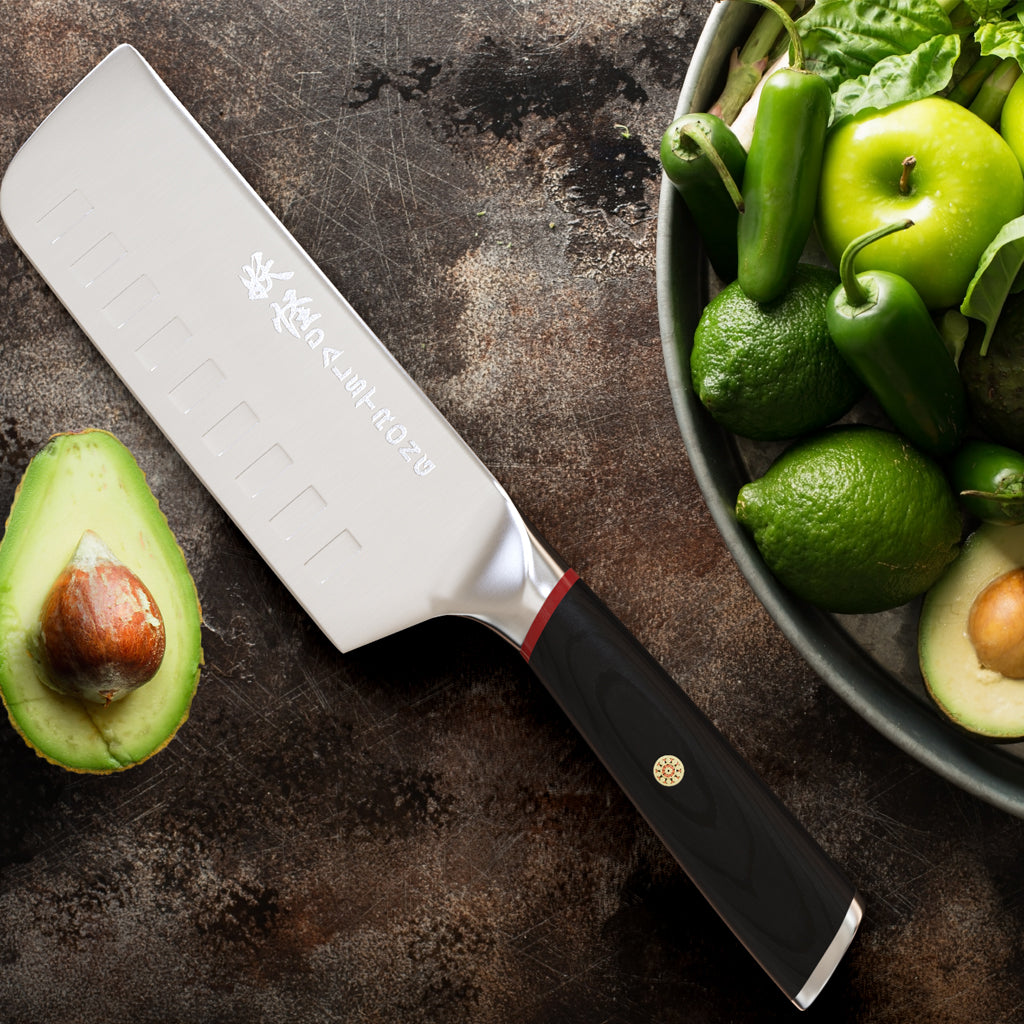 An avocado cut in half with the seed still intact next to a nakiri knife and bowl of green vegetables