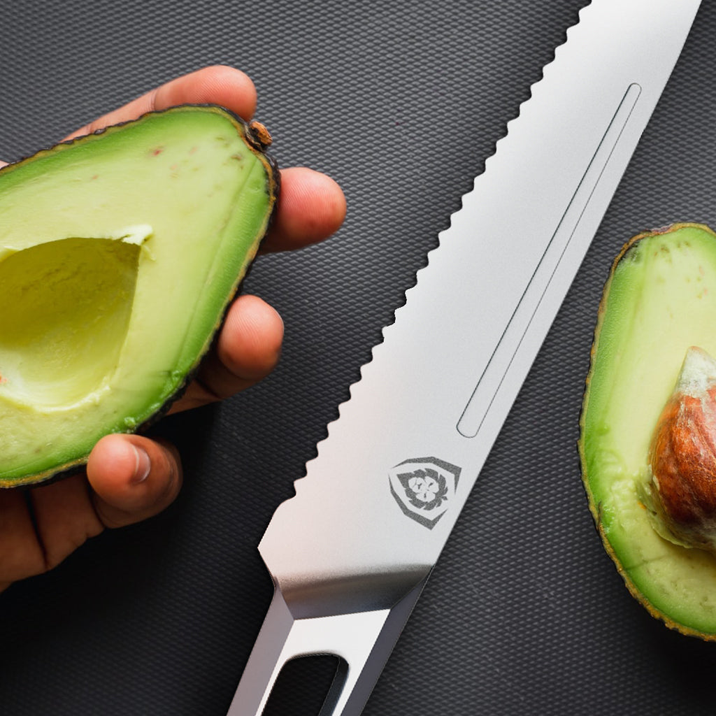 A hand holding an avocado chopped in half next to a stainless steel serrated knife