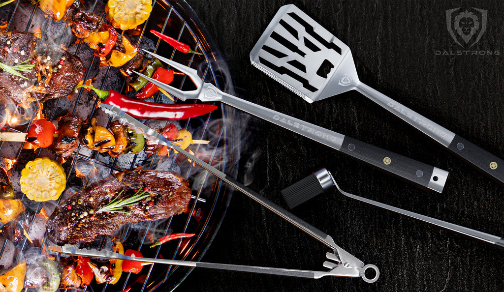 Metalic BBQ Tools hanging off an open grill that's cooking different meat and vegetables