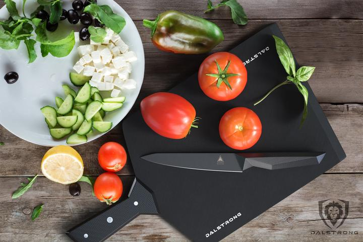 A plate of sliced cucumber and cheese next to a black cutting board with full tomatoes and a black paring knife on it