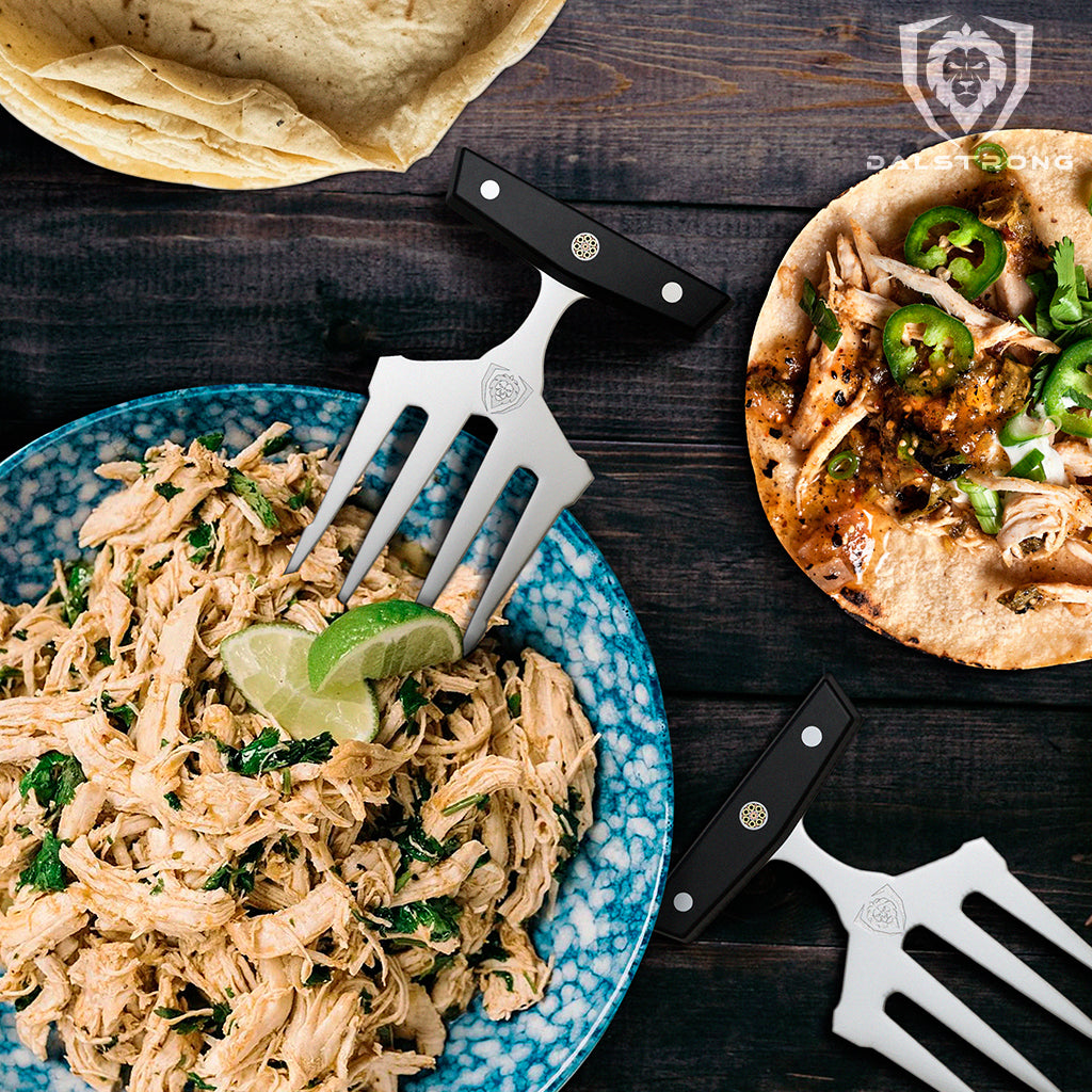 Meat shredding claws beside a plate of pulled chicken and a small tortilla