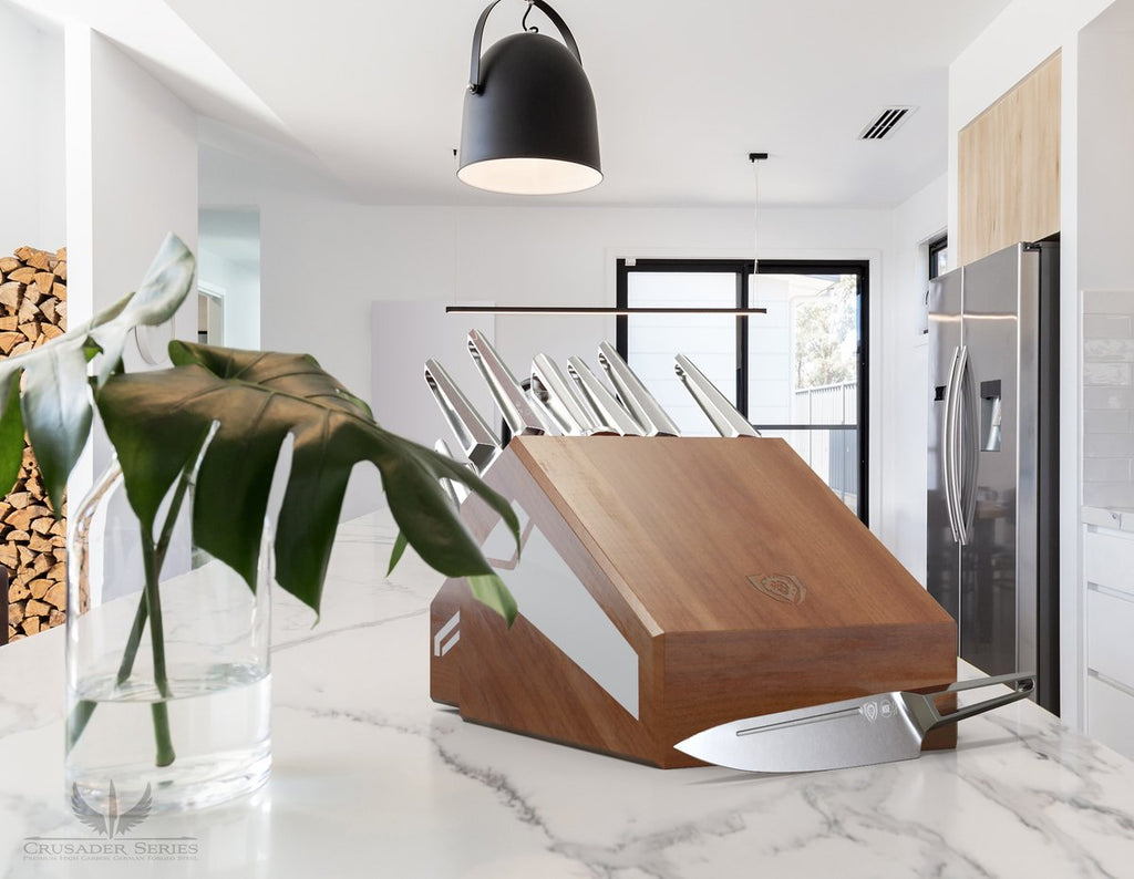 Marble kitchen counter top with vase and wooden knife block that has eighteen pieces in it