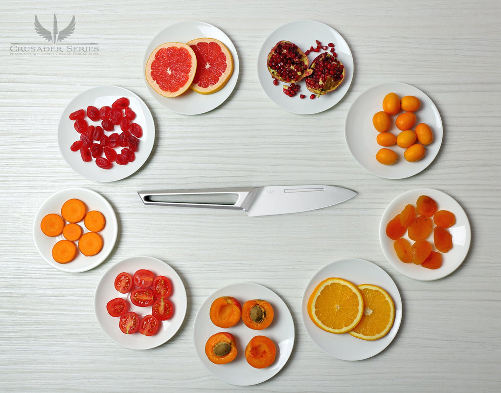 Stainless steel paring knife with hollow handle surrounded by small plates of chopped fruit and vegetables