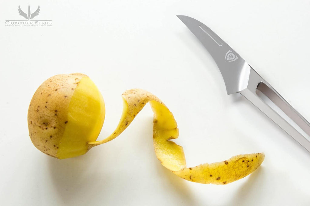 Peeled potato on a white surface next to a stainless steel paring knife with a hollow handle