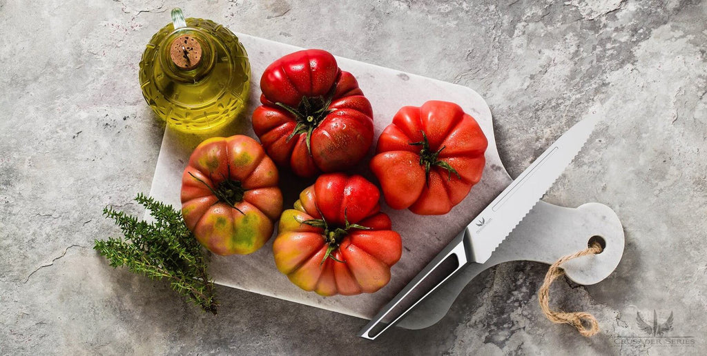 A serrated knife on a cutting board next to four red peppers