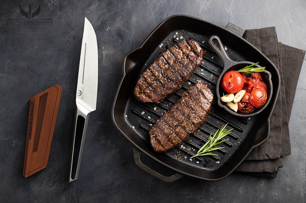 Stainless Steel Knife beside a grill pan thats cooking two steaks and some tomatoes