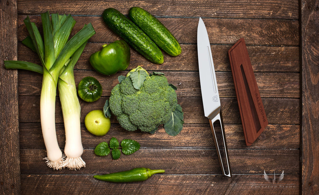 Green vegetables on a wooden surface next to a sharp stainless steel utility knife