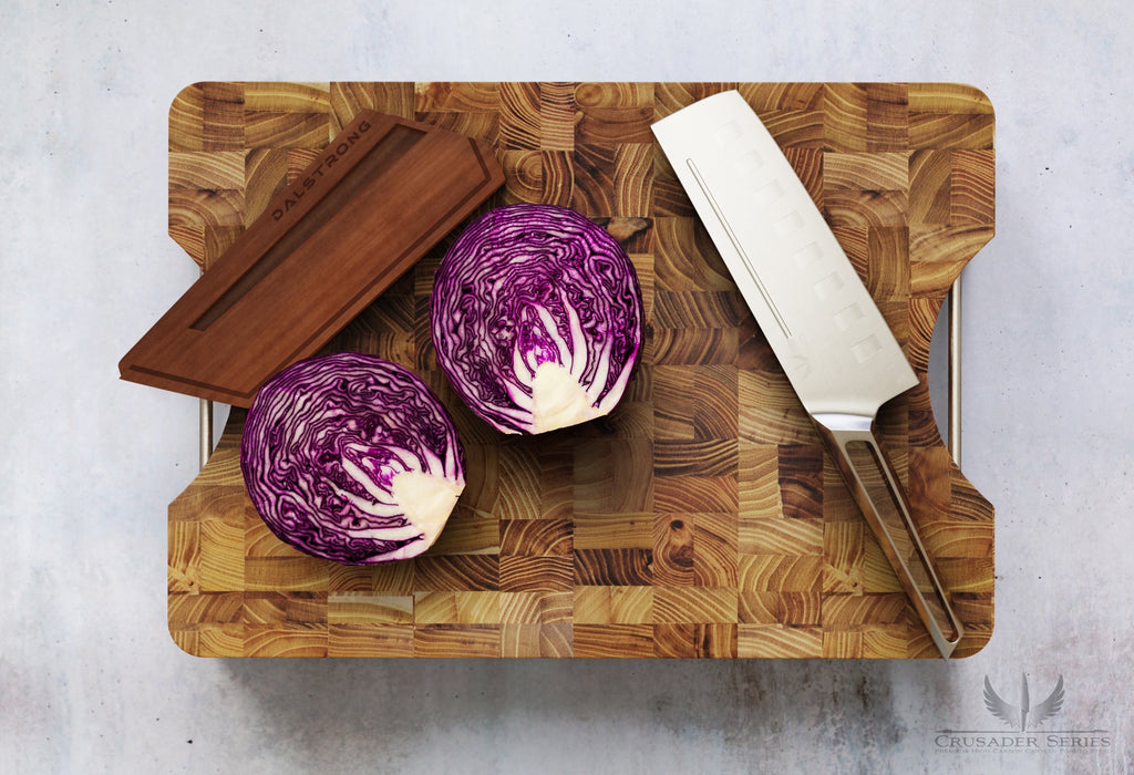 Stainless Steel Nakiri Knife on a large teak cutting board next to a purple cabbage cut in half