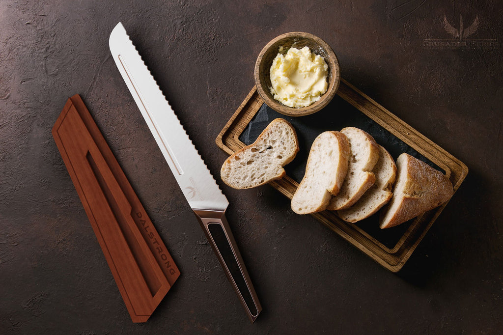 Sliced loaf of bread on a dark surface next to a small portion of butter and a stainless steel bread knife