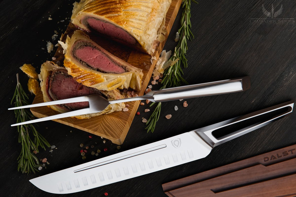 Carving knife with hollow stainless steel handle next to sliced meat and a carving fork