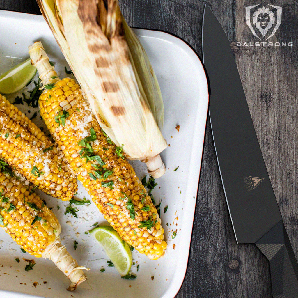 A white baking dish of corn on the cob next to a black kitchen knife