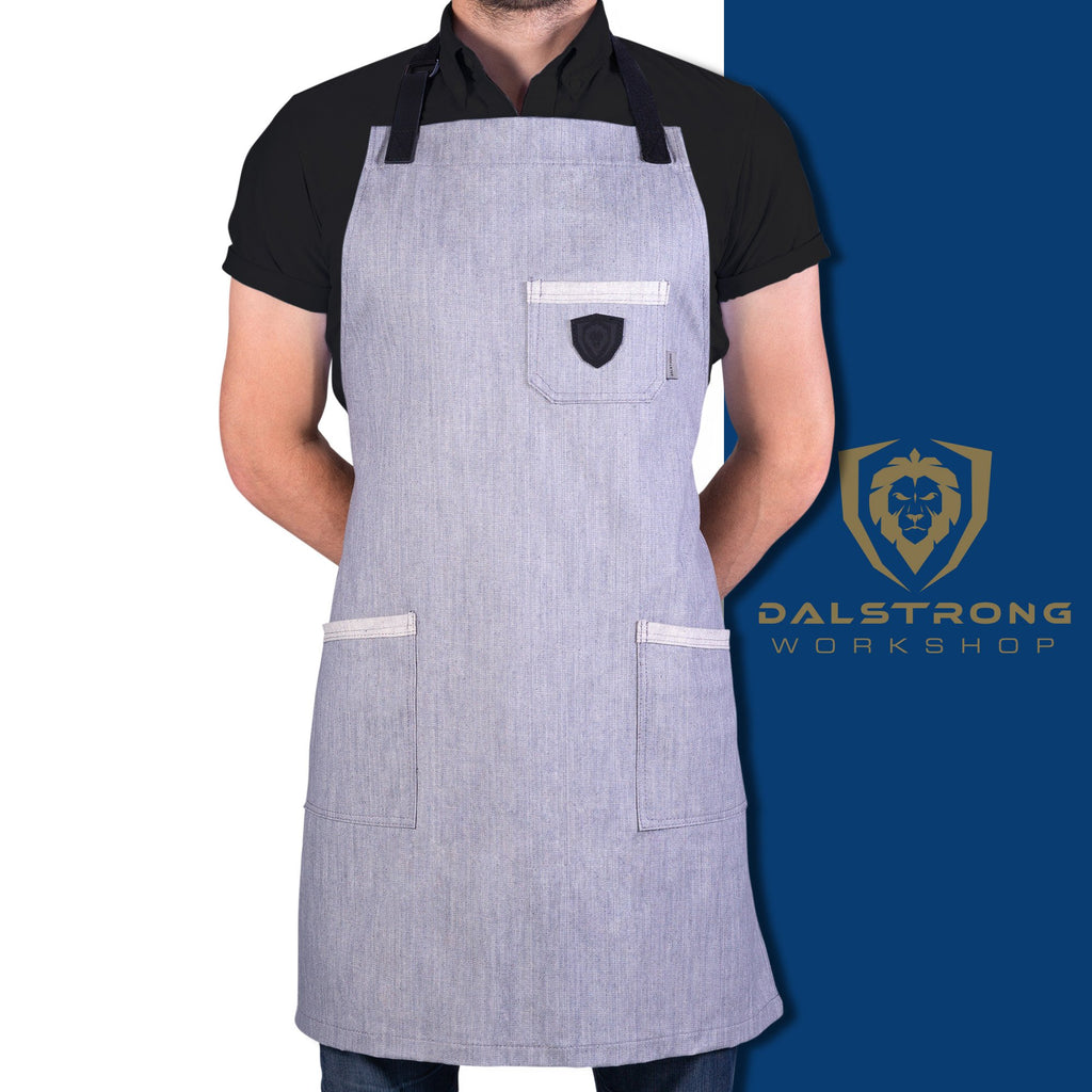 "Man standing with his hands behind his back displaying ""The Gandalf"" grey denim apron with a white and blue background and Dalstrong logo"