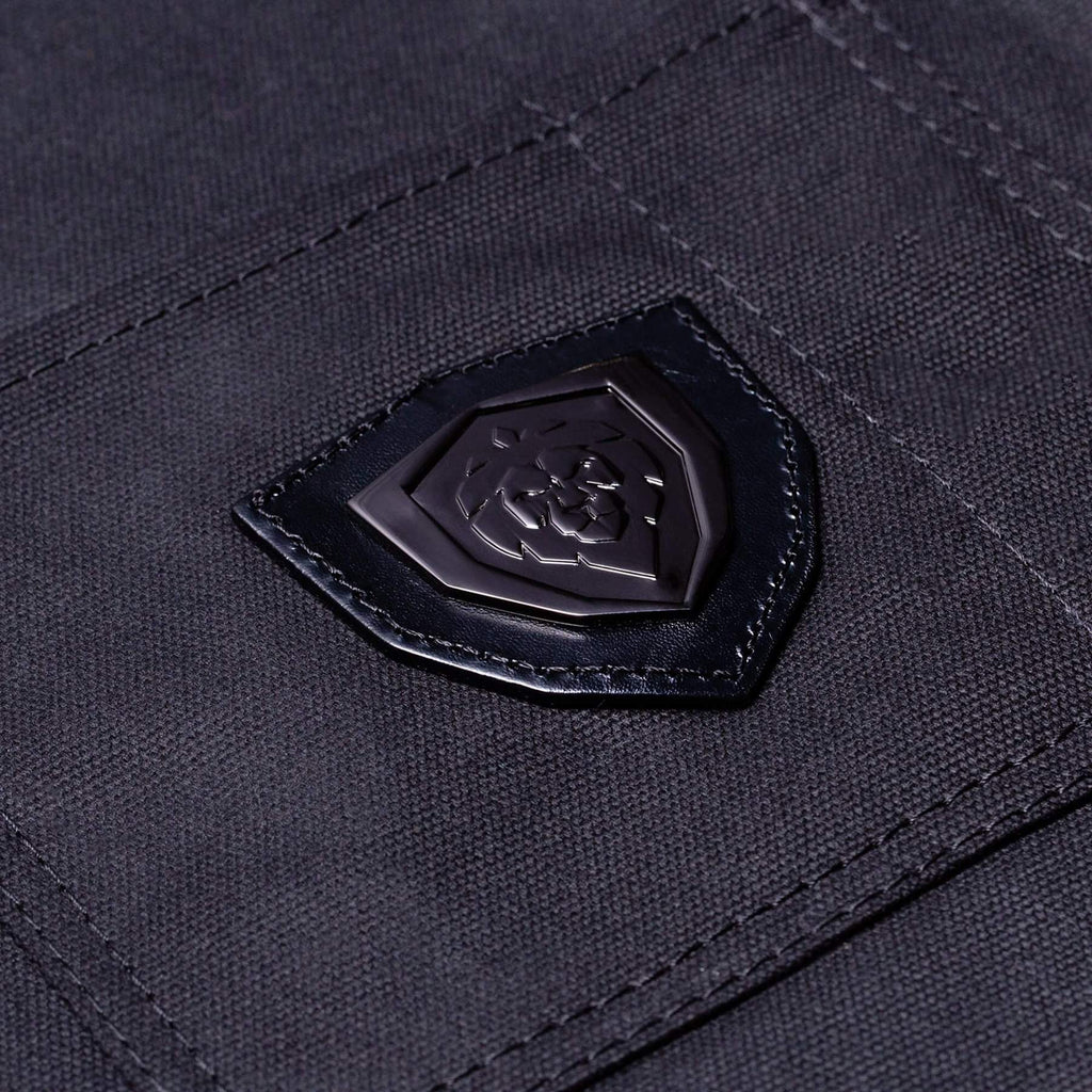 Dark leather lion logo stitched on to the pocket of a chef apron
